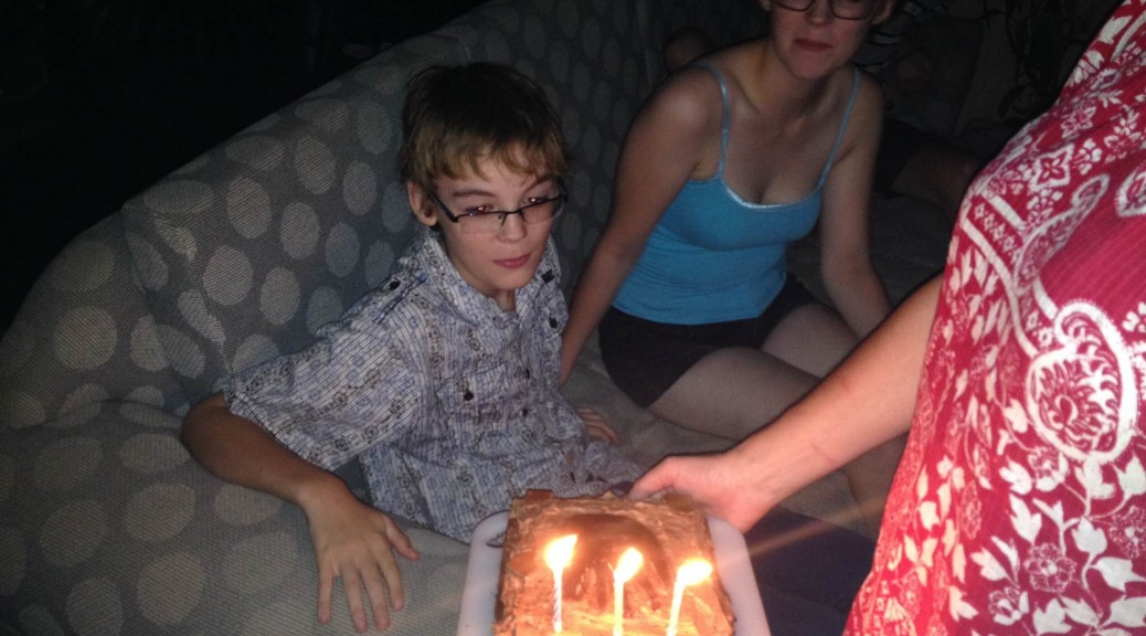 Tom blowing out his candles
